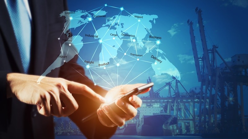 Businessman using mobile phone to manage global logistics and trade